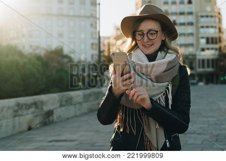 Sunny autumn day, backlight. Young attractive woman travels in hat and eyeglasses stands on city street, uses smartphone. Hipster girl is looking for road, sights. Vacation, adventure, trip.