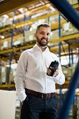 Warehouse worker or supervisor with barcode scanner. A mobile handheld PC with barcode scanner. poster
