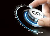 Man turning a carbon dioxyde knob to reduce emissions. CO2 reduction or removal concept. Composite image between a hand photography and a 3D background. poster