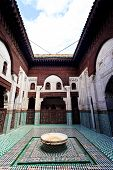 Meknes Morocco: Interior courtyard with fountain of madrasah Muslim school in Meknes Morocco. poster