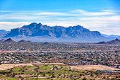 With an aerial view above swimming pools and golf courses loom the Superstition Mountains in Apache Junction, Arizona poster
