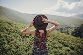 wanderlust and travel concept. stylish traveler woman in hat looking at mountains. hipster girl traveling on top of mountain, raising hands. space for text. atmospheric moment poster