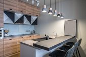 Modern kitchen with white walls and luminous hanging lamps. There is a light kitchen island with a sink and gray tabletops and dark chairs, wooden lockers, oven, stove, chrome kettle, coffee maker. poster