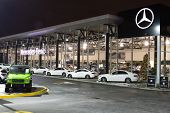 Vancouver BC, Canada - January 9, 2018: Office of official dealer Mercedes-Benz. Mercedes-Benz is a German automobile manufacturer Night shot all sings and inside of the building is illuminated. poster