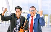 Interracial businessmen exulting looking at camera outdoor - Successful couple of multiracial men fist pump gesture standing outside - Multicultural concept of teamwork , success, business and triumph poster