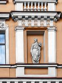 Architectural details balconies, pilasters, arches, rosettes, cornices, busts, a statue in a niche, white patterns on the facade of an ancient building in the center of St. Petersburg on the Griboedova Canal poster