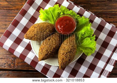Fried Kibbeh With Tomato Sauce On A Plate, Over Rustic Wooden Table. Top View