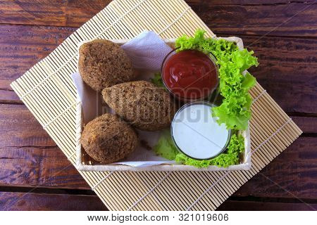 Fried Kibbeh With Tomato Sauce In A Basket, Over Rustic Wooden Table