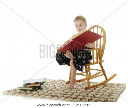 An adorable preschooler reading a big book while helping support it with her toe.  She sits in a child-sized rocker with a stack of books nearby.  On a white background.