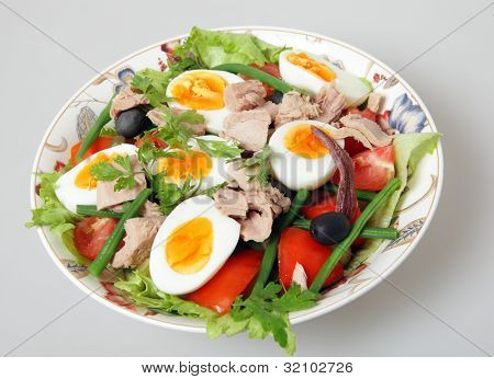 A serving bowl of freshly made traditional nicoise salad - lettuce, potato, tomato, green beans, tuna, anchovies, boiled eggs, capers and black olives, garnished with flat-leaf parsley, over  grey