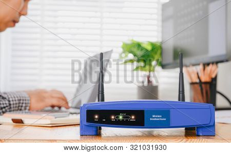 Wireless Router And Man Using A Laptop In Office. Router Wireless Broadband Home Laptop Computer Pho