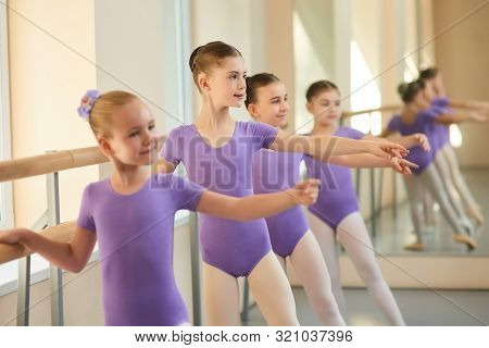 Young Ballerinas Standing In Row And Practicing. Cute Little Ballet Dancers Rehearsing Some Dance Mo