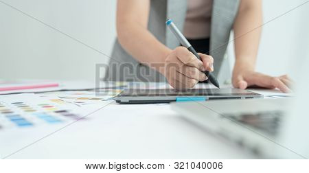 Graphic Designer At Work. Color Swatch Samples. Artist Drawing Something On Graphic Tablet At The Of