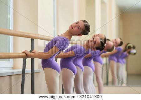 Ballerinas Perform Exercises On A Ballet Barre. Cute Teen Ballerinas Doing Different Exercises Using