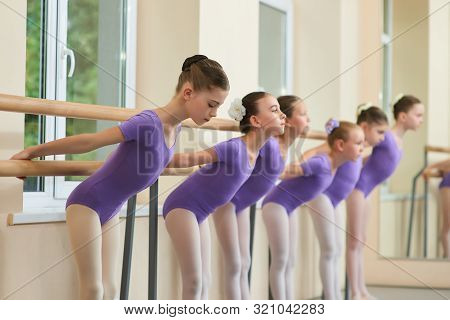 Beautiful Young Ballerinas Ballet Workout. Lovely Ballet Dancers Doing Exercises At Ballet Barre In