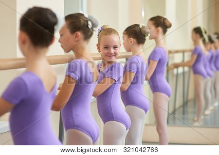 Young Ballerinas Rehearsing Near Ballet Barre. Cute Ballerinas Standing In Row And Practicing Ballet