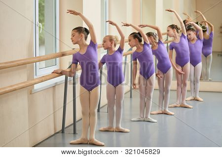 Kids Rehearsing At Ballet Dance School. Group Of Girls Practicing Ballet At Ballet Barre. Childrens