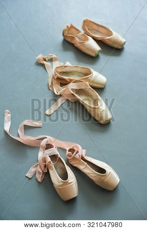 Pink Pointe Shoes With Satin Ribbon. Ballerinas Footwear For Training On Grey Background. Three Pair