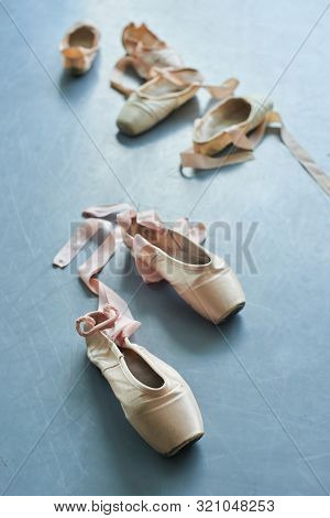 Pair Of Old Ballet Shoes On Grey Background. Ballerinas Used Pointe Shoes With Satin Ribbon. Ballet