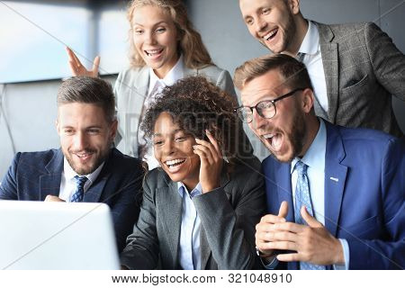 Happy Business People Laugh Near Laptop In The Office. Successful Team Coworkers Joke And Have Fun T