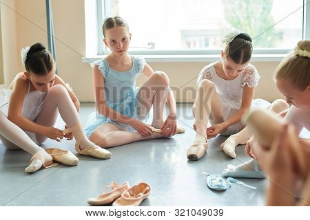 Young Ballerina Sitting On Floor And Looking At Camera. Group Of Beautiful Young Ballerinas Putting
