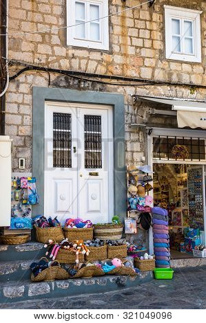 Hydra, Greece - 16 August 2019: Souvenir Shop, Narrow Traditional White Street In The Town Of Hydra,