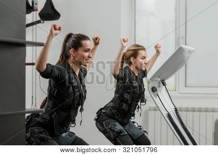 Two Fit Women In Ems Suits Doing Squatting Exercise