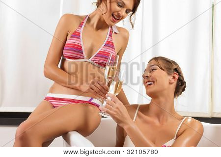 Wellness and Spa - young beautiful woman with her female friend is enjoying a glass of champagne in bathtub poster