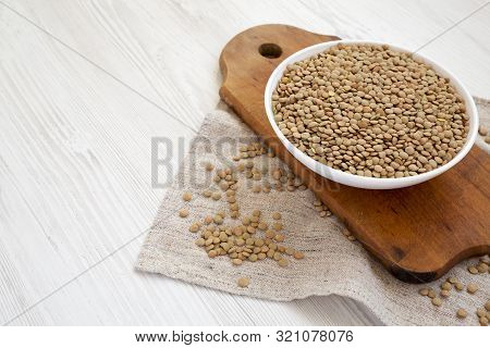 Organic Green Lentils In A White Bowl On A White Wooden Background, Side View. Copy Space.
