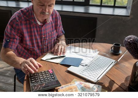Senior Hispanic Man Busy Doing Calculation, Counting Money And Bills At Home.