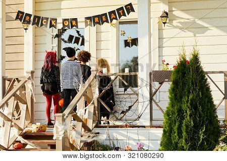 Back View Of Children Trick Or Treating On Halloween, Kids Standing On Porch Knocking On Doors Of De