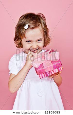 Alegre niña sosteniendo rosa presente en las manos