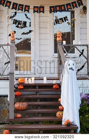 Background Image Of Decorated House On Haloween With Trick Or Treat Banner Above Door, Copy Space