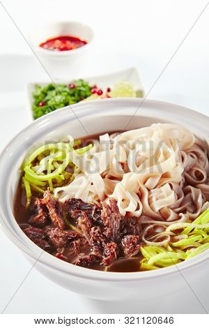 Traditional Vietnamese soup Pho Bo with beef meat, rice noodles, sturdy broth and a set of hot spices isolated on white background. Clear veal bouillon with noodle, meat and vegetables close up