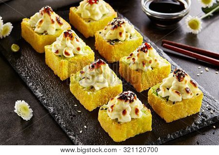 Hot roll in tempura with baked cheese cap and unagi sauce. Sushi restaurant menu item. Traditional japanese appetizer, asian cooking. Delicious eastern appetizer on wooden platter close up