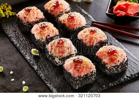 Baked roll with shrimp and masago caviar cap. Traditional sushi restaurant dish, menu item. National japanese cuisine appetizer. Delicious oriental snack, gourmet seafood on wooden platter closeup