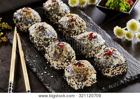 Sesame roll with baked masago caviar cap closeup. Sushi restaurant menu item. Traditional japanese cuisine dish. Delicious oriental food, gourmet appetizer on wooden platter and chopsticks