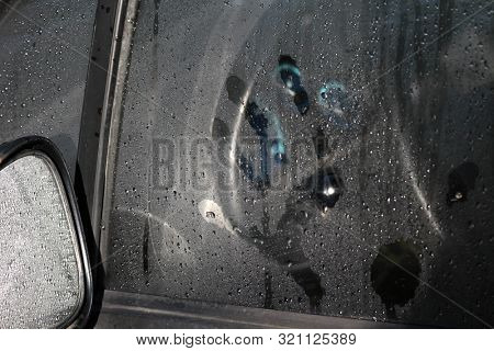 Imprint of a male hand on a car glass