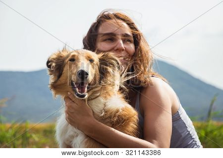 Woman Hugging Scotch Collie Dog In Meadow. Woman Hugging Scotch Collie Dog In Nature. Close Up Of Sc