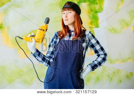 Helpless Middle Age Female Worker Holds Drill In Hand.serious Builder Woman Using Electric Screwdriv