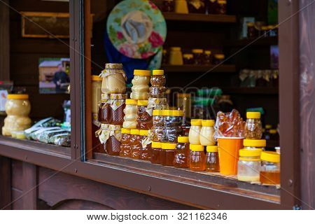 Small Jars Of Golden And White Honey In The Form Of Bears Stand On A Wooden Counter In The Market Du