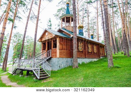 An Old Antique Wooden Church Or Monastery In The Forest Among A Large Number Of Trees With Crosses A