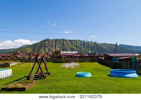 A Large Swing Made Of Wood And An Inflatable Rubber Pool On A Green Grass Lawn In The Courtyard Of A