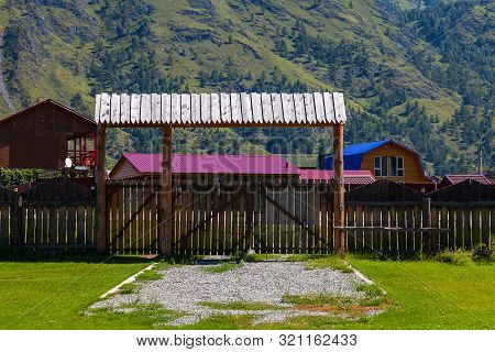 Wooden Gate With A Fence And A Canopy From The Rain On A Country Villa In The Mountains With A Green
