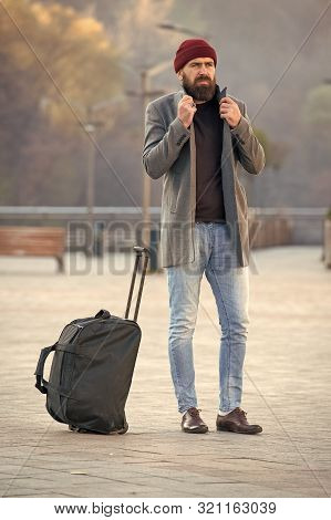 poster of Looking for accommodation. Man bearded hipster travel with big luggage bag wait for taxi bring him to hotel. Travel tips. Traveler with suitcase arrive travel destination. Hipster ready enjoy travel.