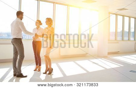 Businesswoman with secretary shaking hands with executive manager in office with yellow lens flare in background