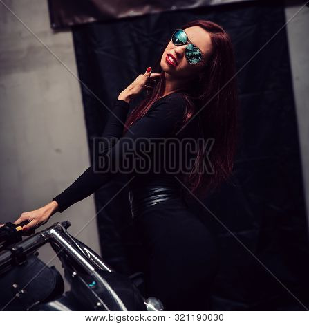 Fashionable Young Woman Standing Near Black Trike
