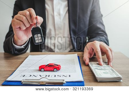 Sale Agent Giving Car Key To Customer And Sign Agreement Contract, Insurance Car Concept.