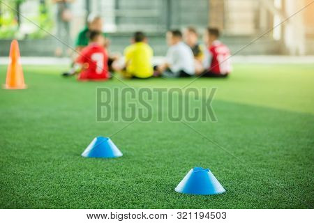 selective focus to blue marker cones are soccer training equipment on green artificial turf with blu