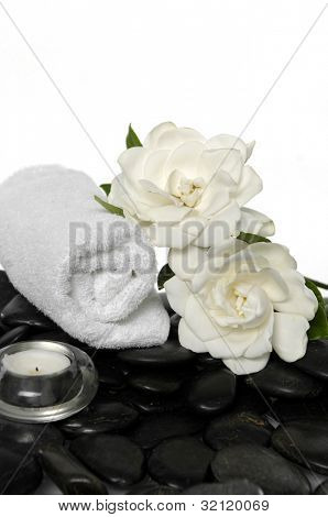 Two gardenia flower and towel on pebbles